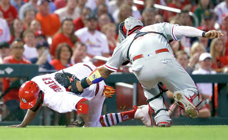 The Cardinals' Dexter Fowler, left, is tagged out by Phillies catcher Jorge Alfaro after being caught between third and home during the seventh inning Thursday in St. Louis. Photo:       Jeff Roberson | AP