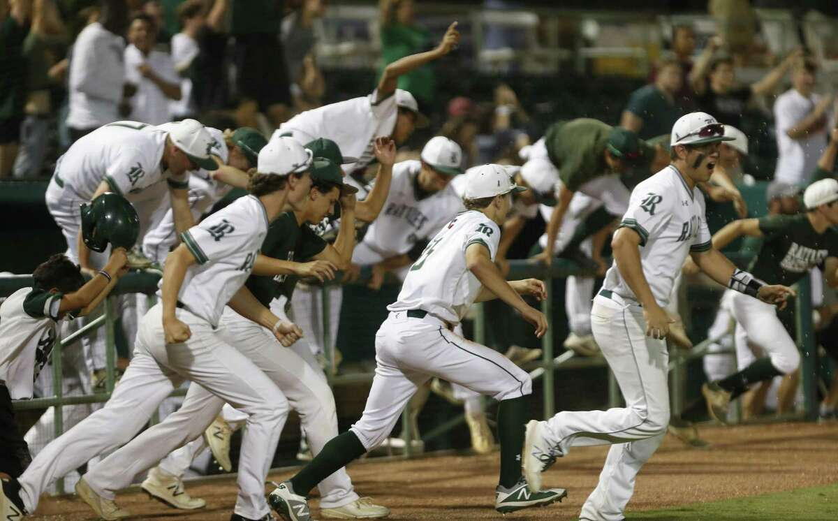 Reagan players storm the field after the last out from Game 1 of a Class 6A third-round high school baseball playoff series between Reagan and Austin Lake Travis at Wolf Stadium on Thursday, May 17, 2018.