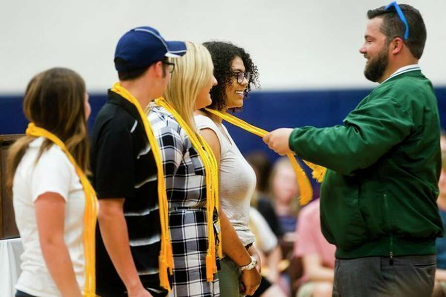 Meridian Principal Patrick Malley places honors cords on the shoulders of Meridian senior Madison Murray during the annual Decision Day event on Thursday at Meridian Early College High School. For more photos from Decision Day, go to www.ourmidland.com. (Katy Kildee/kkildee@mdn.net)