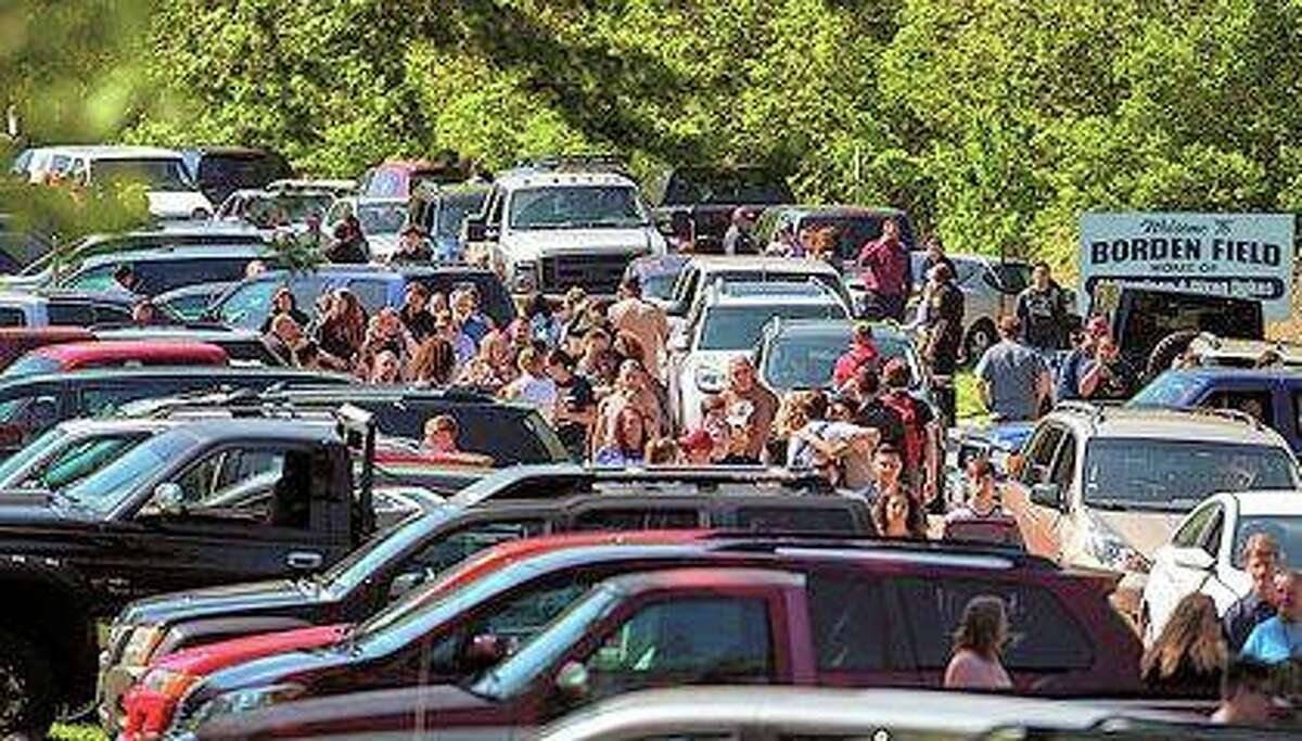 Parents wait down the road to meet their children following a shooting at Dixon High School on Wednesday. A 19-year-old who showed up at his former high school and opened fire on a police officer working there was shot by the officer and taken into custody.