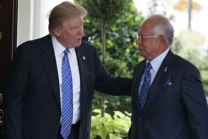 FILE - In this Sept. 12, 2017, file photo, U.S. President Donald Trump, left, greets Malaysian Prime Minister Najib Razak at the White House in Washington. Malaysia's image as a striving, modern nation that upholds the rule of law has been undermined by an epic corruption scandal at state investment fund 1MDB. Najib, who set up the fund, is facing May 9, 2018 national elections that will test his legitimacy. (AP Photo/Evan Vucci, File)