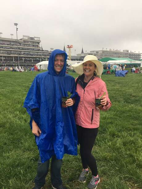 Maggie Gordon and John Swatkowski stand in the rain for the 144th running of the Kentucky Derby, in Louisville, KY, May 5, 2018. Their outfits were not quite what they'd planned to wear. Photo: Contributed / Contributed