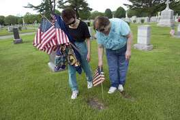 Suzanne LaBella and her sister Patti LaBella volunteer with member of the Veterans of Foreign Wars Post 9617-Springdale and other organizations as they place American flags on veterans graves at St. John's Cemetery in honor of Memorial Day on Saturday, May 21, 2011.