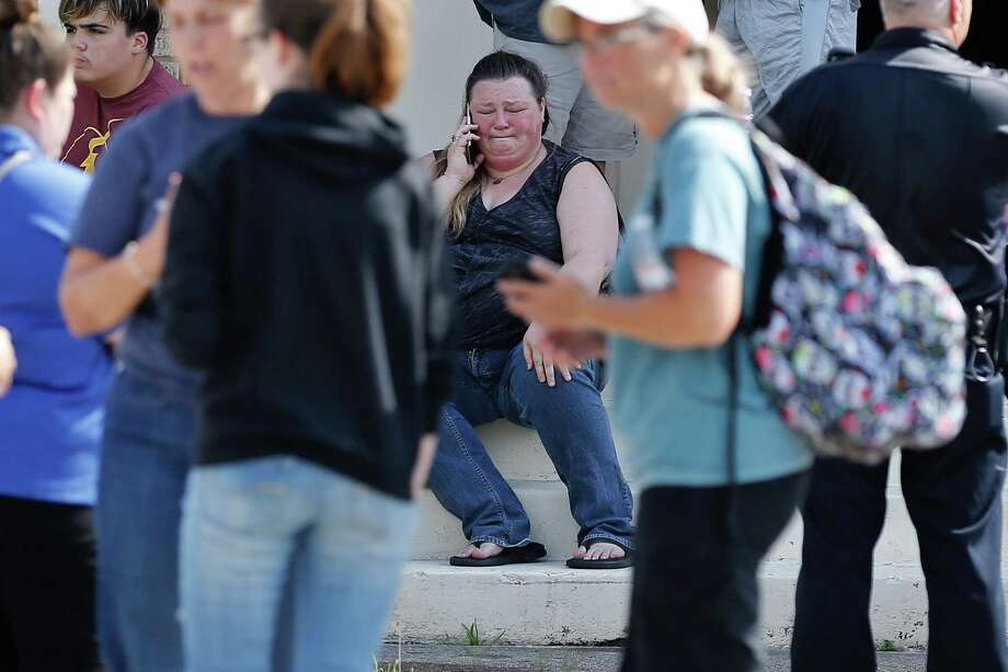 Pamela Stanich, center, tries in vain to call her son Jared Black, a Santa Fe High School junior, on Friday outside the Alamo Gym, where parents and students wait to be reunited after a mass shooting at the school. Photo: Michael Ciaglo