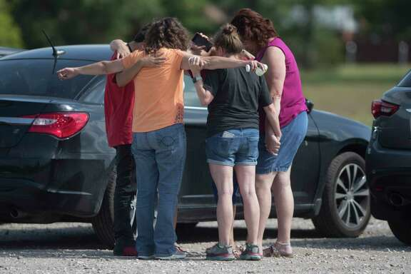 Parents of Santa Fe High School students join in prayer at the parking lot the Arcadia First Baptist Christian School accompanied with residents after a shooter open fire at the high school, Friday, May 18, 2018, in Santa Fe.