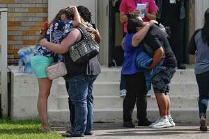 People embrace outside the Alamo Gym where students and parents wait to reunite following a shooting at Santa Fe High School Friday, May 18, 2018 in Santa Fe.