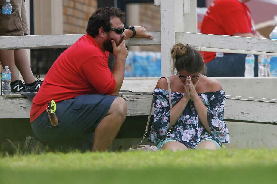 A woman prays in the grass outside the Alamo Gym where parents wait to reunite with their kids following a shooting at Santa Fe High School Friday, May 18, 2018 in Santa Fe. Photo: Michael Ciaglo, Houston Chronicle