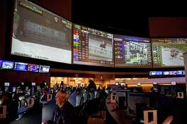 Bettors place bets at Winners Sports Haven in New Haven. A change in state law to allow sports gambling would not be a major revenue source, according to Fitch Ratings.