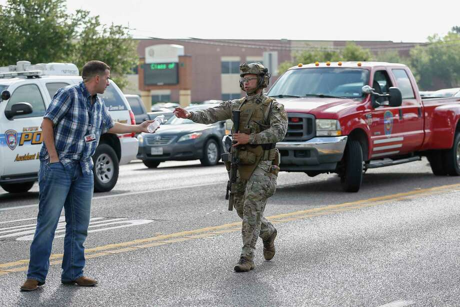 PHOTOS: From the scene of Santa Fe High School A law enforcement officer reaches for water as he responds to an active shooter in front of Santa Fe High School Friday, May 18, 2018, in Santa Fe. Photo: Steve Gonzales, Houston Chronicle / © 2018 Houston Chronicle