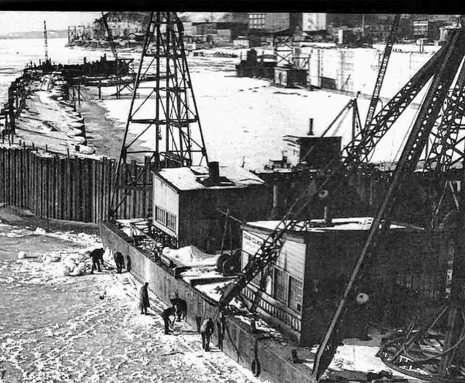 The winter of 1936-37 was hard on the cofferdam for the auxiliary lock. Ice pressure was too great for the upper end and it collapsed. Here, men are seen sawing along the barges at the lower end to relieve the pressure and avoid damage to the hulls. The buildings visible in the background include the flour mills and homes high up on Prospect Street. The bluffs can also be seen. Photo:       File Photo
