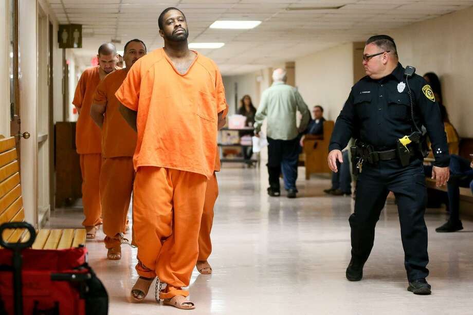 Deandre Dorch (front left) is led toward the Felony Impact Court, presided by Judge Laura Parker, in the Bexar County Courthouse for sentincing on Friday, May 18, 2018. Dorch, convicted of injury to a child by omission and abandonment of a child in the horrific case of two children who were tied up like dogs and left in the backyard of a home in Northeast Bexar County, received a sentence of 65 years in jail but will be eligible for parole in 30 years. MARVIN PFEIFFER/mpfeiffer@express-news.net Photo: Photos By Marvin Pfeiffer / San Antonio Express-News / Express-News 2018