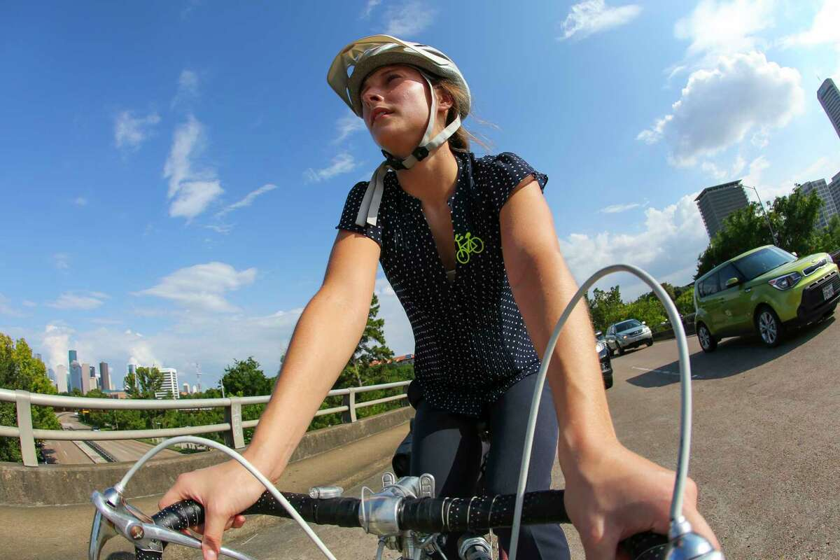 Jessica Wiggins, who works for the non-profit organization BikeHouston, crosses Buffalo Bayou on Montrose Blvd. while commuting from Montrose to the Heights, Thursday, July 3, 2017.