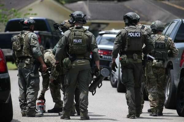 Police and FBI carrying tools towards a home believed to be related to the fatal school shooting earlier in the day at Santa Fe High School on Tuesday, May 18, 2018, in Santa Fe, TX.
