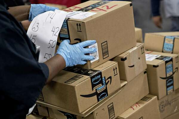 An employee arranges Amazon.com Inc. packages before delivery at the United States Postal Service Joseph Curseen Jr. and Thomas Morris Jr. processing and distribution center in Washington.