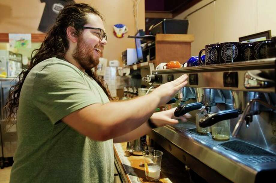 Josh Trochet, a barista at Espresso Milano, makes a drink for a customer on Tuesday. The coffeehouse, located at 137 Ashman St. in downtown Midland, is celebrating its 25th anniversary this month. (Katy Kildee/kkildee@mdn.net)