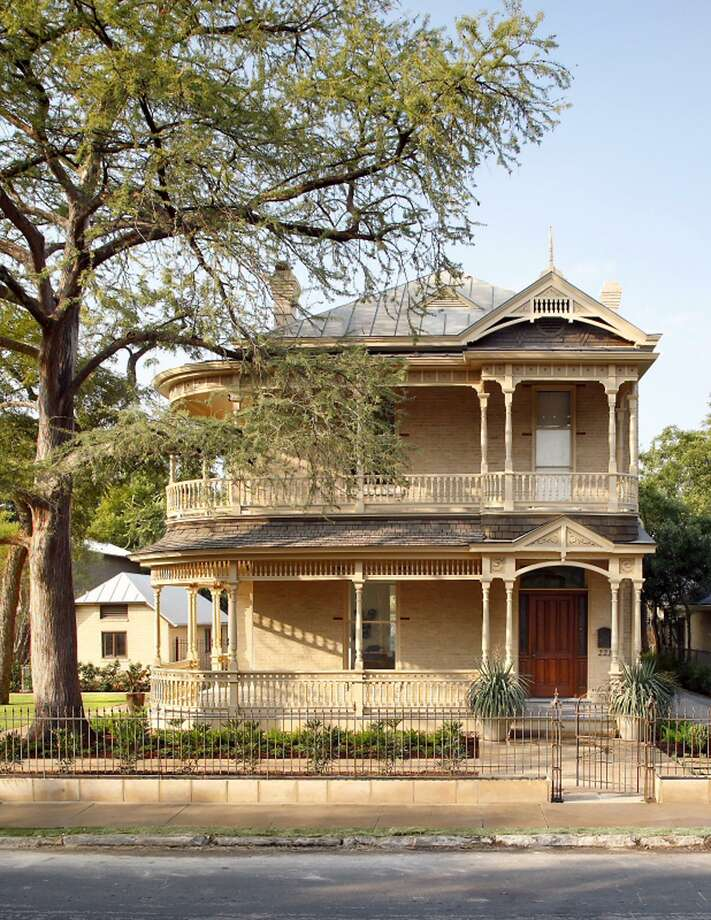 Backing up to the San Antonio River, this house has two levels of wraparound porches. During a restoration several years ago by architect Jim Poteet, it was repainted to match the color of the building's bricks more closely. Photo: Courtesy Ryann Ford / Poteet Architects