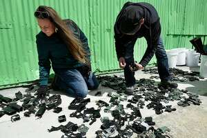 Artists Natasha McCray and Kevin Byall pick through pieces of disassembled guns outside of American Steel Studios in Oakland, Calif., Saturday April 7th, 2018. The Alameda County District Attorney's Office is partnering with the Robby Poblete Foundation to commission seven sculptures made from disassembled guns.