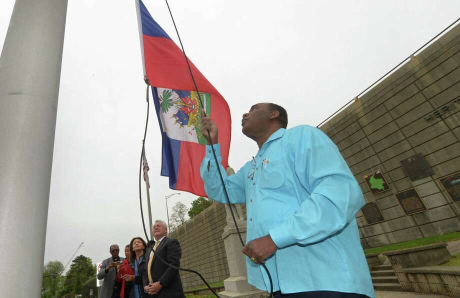 Rahoul Dupervil, right, raises flag during the Haitian flag-raising ceremony at Heritage Wall on Friday May 18, 2018, in Norwalk, Conn. May 18 is Haitian Flag Day and marks the day when Haiti became the first country in the Caribbean to declare independence from its colonizers and become governed by its former slaves. Photo: Erik Trautmann / Hearst Connecticut Media / Norwalk Hour