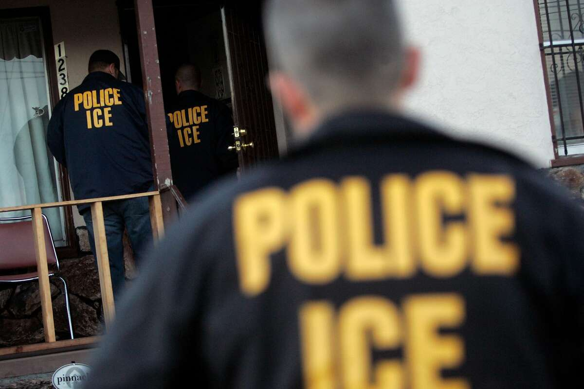 FILE - ICE agents enter a home in Oakland, CA.
