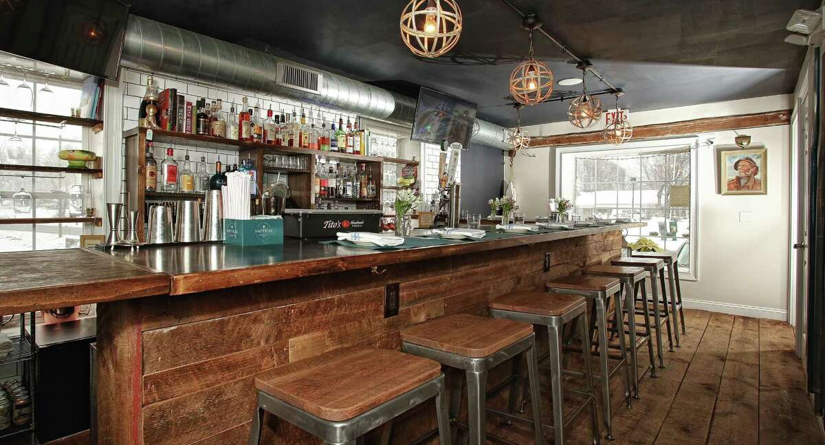 The bar at Lucas Local in Newtown is made of repurposed barn wood and a steel top, which is meant to show its age. The stools are topped with industrial steel.