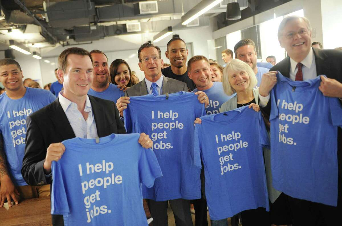 Front row, from left, Indeed SVP and CFO Dave O'Neill, Gov. Dannel P. Malloy, state economic development Commissioner Catherine Smith, and Stamford Mayor David Martin hold up company t-shirts with employees after speaking at the Indeed headquarters at 177 Broad St., in Stamford, Conn., on July 12, 2017.