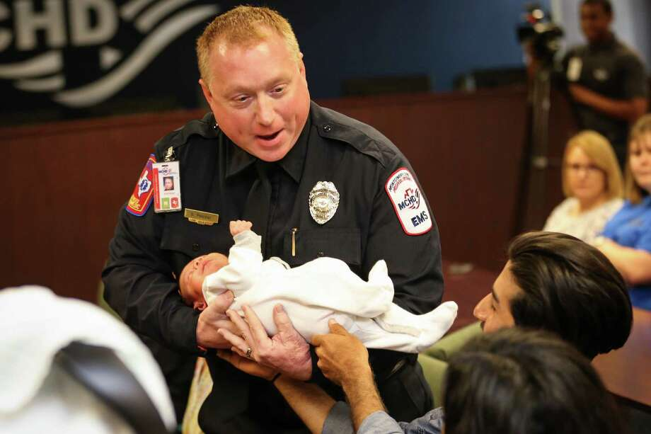 MCHD paramedic Scott Pelczar takes 2-week-old Aaron Santiago Perez, who was delivered in-home by Pelczar, during celebratory presentation on Friday, May 18, 2018, at the Montgomery County Hospital District Administrative Building. Photo: Michael Minasi, Staff Photographer / Houston Chronicle / © 2018 Houston Chronicle