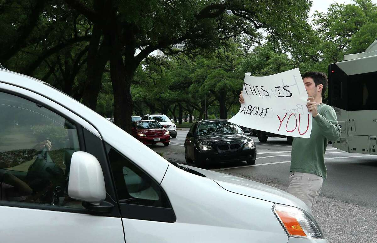 Rice University Bioengineering graduate student Trenton Piepergerdes, 24, holds up a sign toward a motorist that inched to the crosswalk while the pedestrian light was on at the intersection of Sunset Boulevard and Main Street Thursday, May 3, 2018, in Houston. BikeHouston, and university students, faculty, and staff gathered to call attention to the dangerous intersection. A woman was fatally struck by a dump truck at the intersection last week. ( Godofredo A. Vasquez / Houston Chronicle )