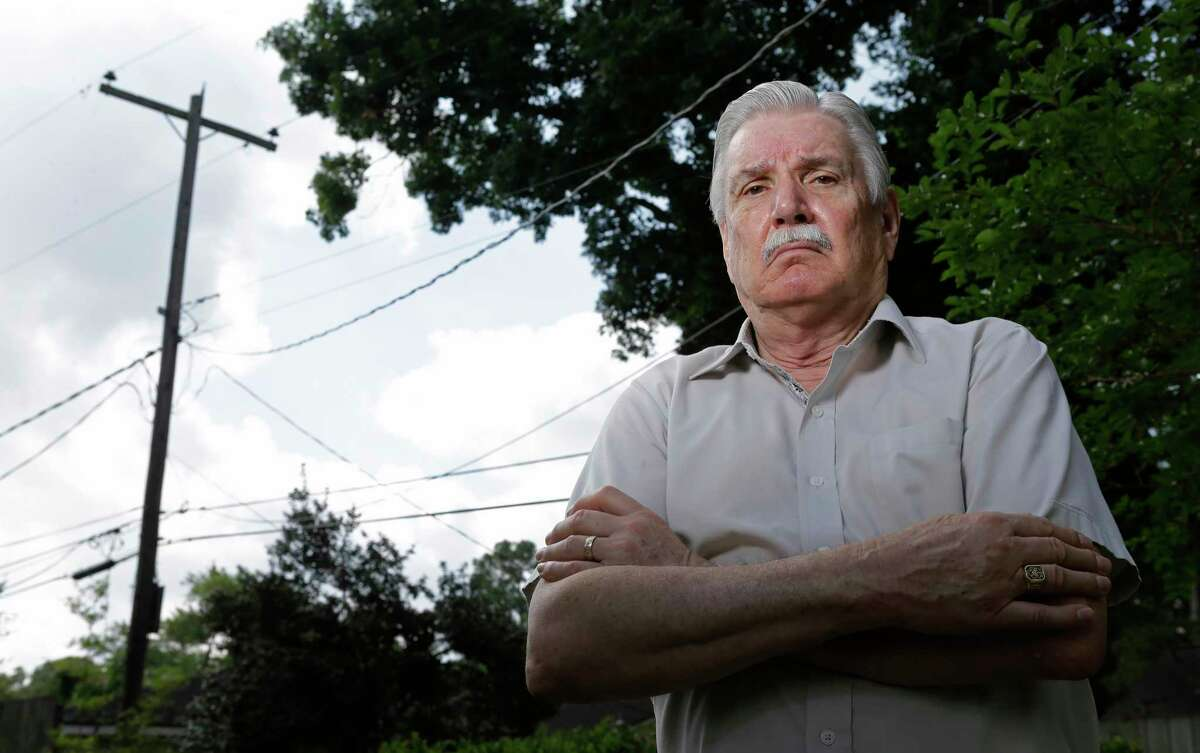 Wayne Herbert stands in his backyard near where he recently spoke to an AT&T lineman, who was working on the utility pole, who told him fiber was all around his home, but not on his block shown Friday, May 18, 2018, in Houston. The lines carry cable, phone, and power. He is annoyed that he can only get Comcast for fast access, as AT&T hasn't brought fiber optic connections to his block yet.