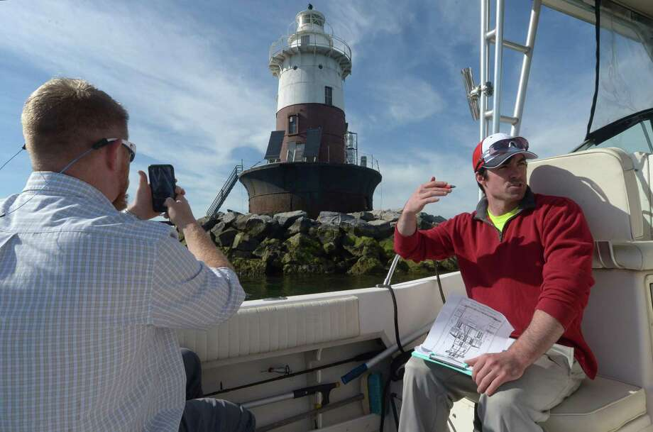 Maritime Aquarium boat captain Travis Mingo and Greens Ledge Light Preservation Society Treasurer Alex Pettee motor away from the lighthouse after giving representatives from the Maritime Aquarium a tour of the recently acquired structure Friday, May 11, 2018, in Norwalk, Conn. $1.5 million dollars have been raised to restore the Greens Ledge Lighthouse and work is slated to begin this summer. Photo: Erik Trautmann / Hearst Connecticut Media / Norwalk Hour