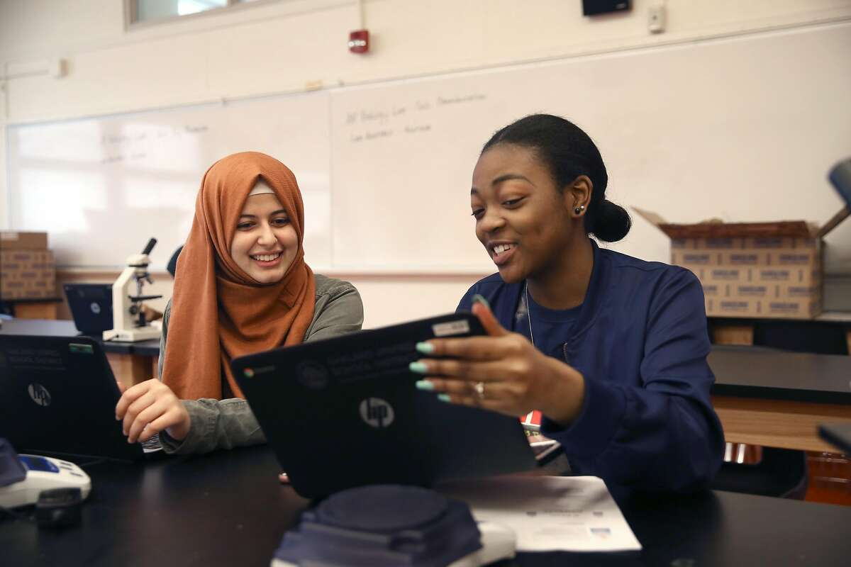 Senior student Haifa Algabri (left) with Neisha Moore in AP biology class as they prep to study fruit flies at McClymonds High School on Friday, May 18, 2018 in Oakland, Calif.