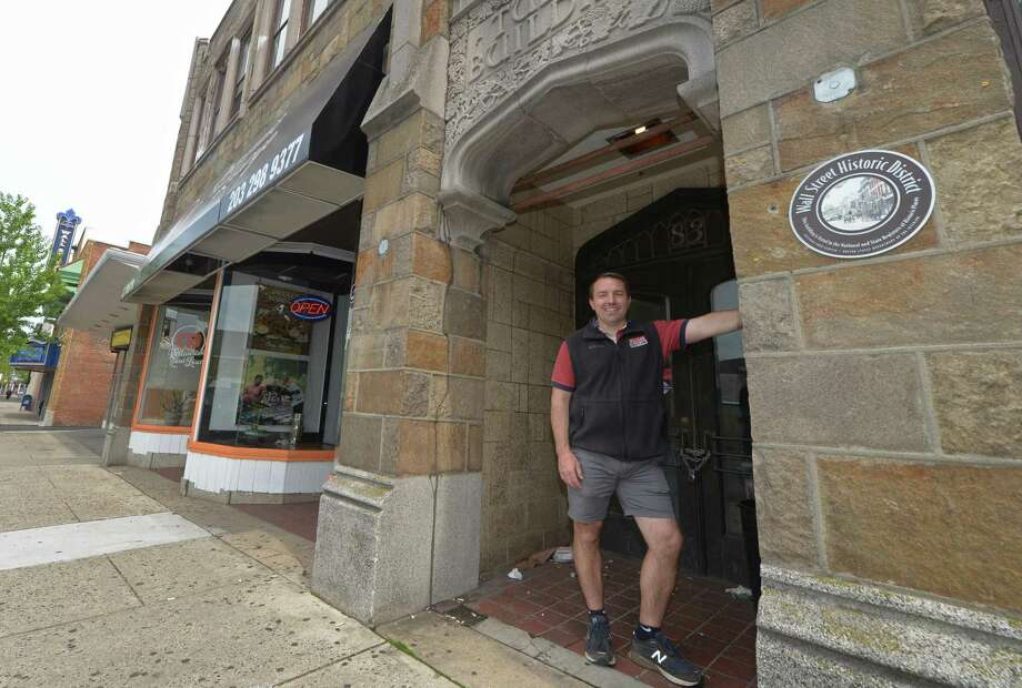 Wall Street neighborhood property owner Jason Milligan walks through the area Friday, May 18, 2018, after a move to close on the Fairfield County Bank Building at 67-69 Wall St. and placing $5 million in escrow to purchase five other nearby properties including 21, 23, 31, Isaac Street and  83 and 97 Wall Street in Norwalk, Conn. As part of his vision to revitalize Wall Street Milligan plans to maintain existing facades and street-level retail while building apartments above within existing buildings. Photo: Erik Trautmann / Hearst Connecticut Media / Norwalk Hour