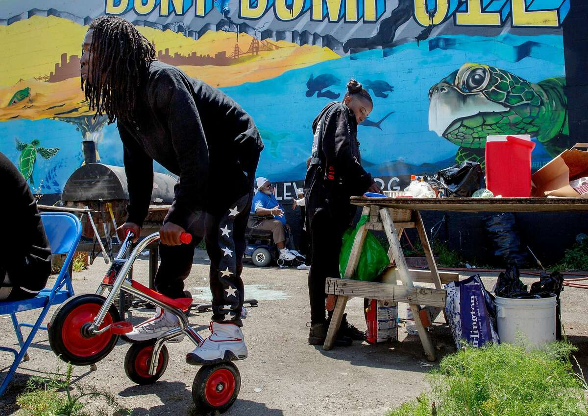 From left: Patrick Joseph on a tricycle as Shanay Rash makes a hot meal during a community cookout at the Bayview Roots Garden, Thursday, May 17, 2018, in San Francisco, Calif.