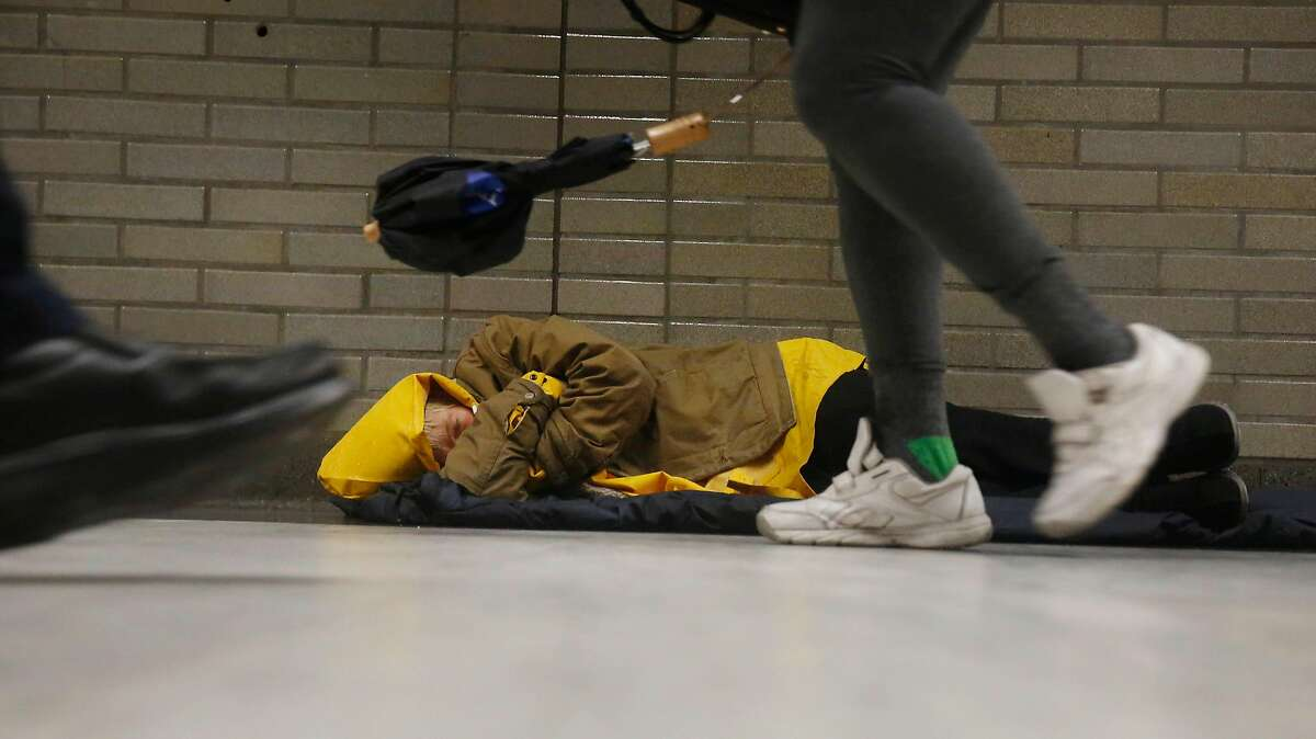 People walk past a person sleeping on the ground at Civic Center Bart station on a rainy day on Monday, January 8, 2018 in San Francisco, Calif.