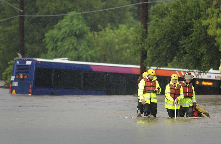 Fire department water rescue team members make their way through the water after checking a VIA bus that was flooded on McCullough just north of Basse. They found nobody in the bus on Saturday morning, May 25, 2013. Photo: Billy Calzada, San Antonio Express-News