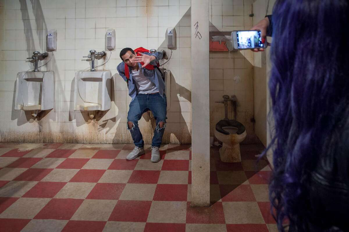 Festival goers take photo of themselves in a bathroom set in the Patty's Pub Flipadelphia venue during the Colossal Clusterfest at Civic Center Plaza in San Francisco, California, USA 2 Jun 2017. (Peter DaSilva/Special to The Chronicle)