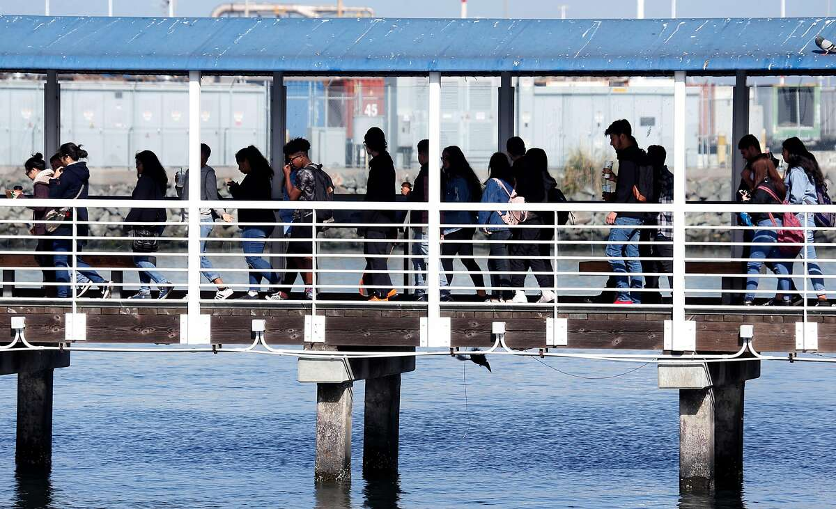 Commuters board a ferry to San Francisco in Oakland, Calif. on Thursday, May 10, 2018. Ferry service would be upgraded if voters approve Regional Measure 3 which would raise area bridge tolls, except on the Golden Gate Bridge, to fund transportation projects throughout the Bay Area.