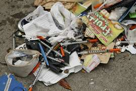FILE - In this Feb. 26, 2016, file photo, a number of syringes are scattered in the remains of a tent city being cleared by city workers along Division Street in San Francisco. San Francisco's mayor says he plans to send a medical team to city streets to distribute a drug that helps stop heroin cravings to homeless addicts. Distributing Suboxone on city streets, which Mayor Mark Farrell says will be the first program of its kind in the country, is the city's latest effort to address heroin addiction. (AP Photo/Eric Risberg, File)