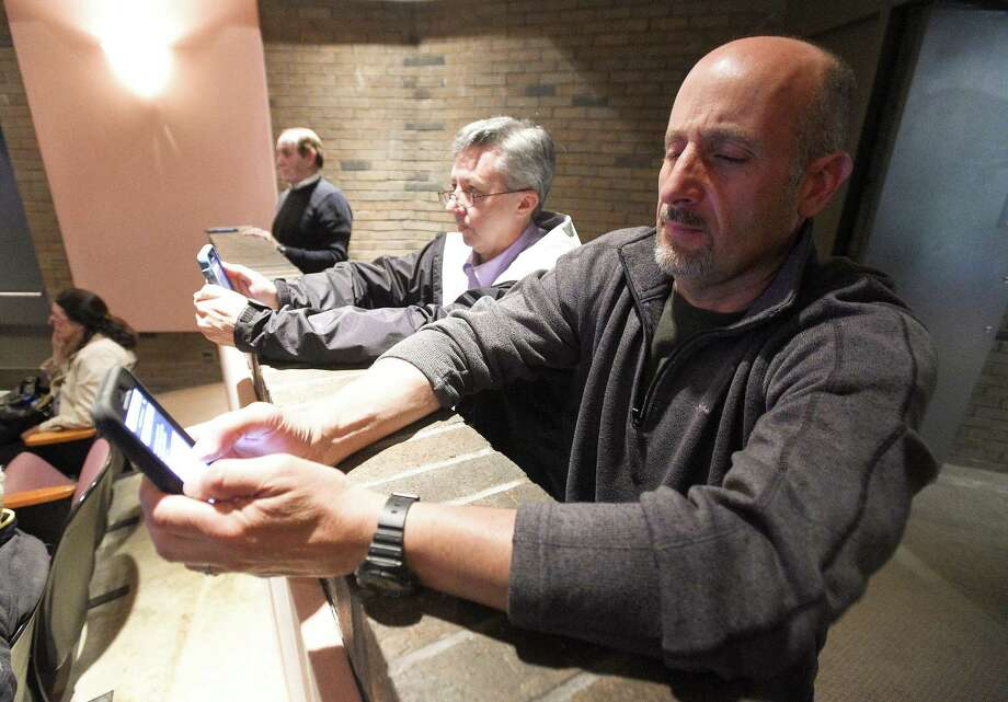 LEFT: John Houseal of Houseal Lavigne Associates, directs residents to interactively participate in a poll. RIGHT: Mike Banks of Old Greenwich, foreground at right, interactively participates in an Greenwich Town Plan of Conservation & Development meeting at the Greenwich Library Cole Auditorium in Greenwich. Photo: Matthew Brown / Hearst Connecticut Media / Stamford Advocate