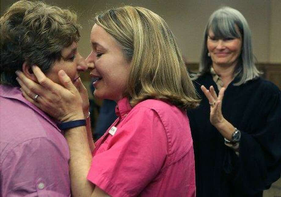 Celeste Branstetter, center, embraces her partner Felice Garcia's face for a kiss after they were married by Judge Karen Pozza at the Bexar County Courthouse on June 26, 2015. Gay couples were able to get their marriage license at the Bexar County Courthouse after the Supreme Court voted in favor of same sex weddings, on Friday, June 26, 2015. Some of the couple were married in the Presiding Court the same day. Photo: /