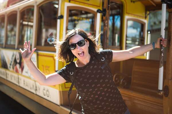 Young happy woman standing in one of the historic cable cars of San Francisco at California Street. Copy space left.
