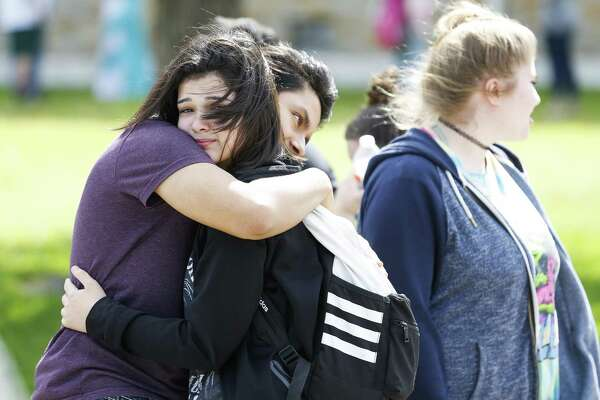 Santa Fe High School student Caitlyn Girouard, second from left, embraces a friend outside Alamo Gym where parents and students wait to be reunited after a mass shooting at Santa Fe High School Friday, May 18, 2018 in Santa Fe.