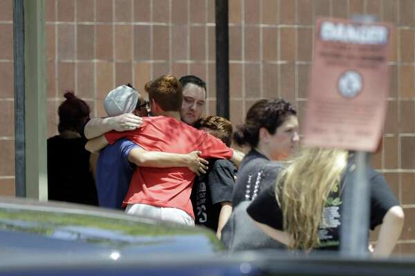 People react outside the unification center at the Alamo Gym, following a shooting at Santa Fe High School Friday, May 18, 2018, in Santa Fe, Texas. (AP