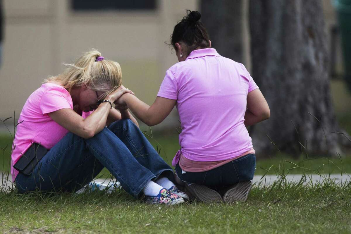 Two women pray outside the family reunification site following a shooting at Santa Fe High School on Friday, May 18, 2018, in Santa Fe, Texas.