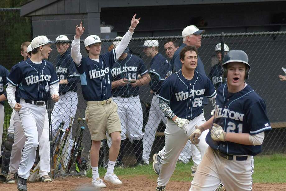 Parker Ward (21) leads the Wilton High celebration after scoring the game-winning run on a walk-off error in the bottom of the ninth inning of the Warriors 5-4 win over Brien McMahon on Friday. Photo: John Nash/Hearst Media Connecticut