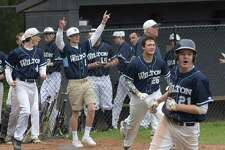 Parker Ward (21) leads the Wilton High celebration after scoring the game-winning run on a walk-off error in the bottom of the ninth inning of the Warriors 5-4 win over Brien McMahon on Friday.