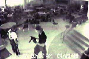 In this April 20, 1999 file photo Eric Harris, left, and Dylan Klebold, carrying a TEC-9 semi-automatic pistol, are seen in a photo made from a security camera image in the cafeteria at Columbine High School, in Littleton, Colo., during their shooting rampage which killed a teacher and 12 students. The mother of Columbine killer Dylan Klebold says she has been studying suicide in the decade since the high school massacre but had no idea her son was suicidal until she read his journals after his death.  (AP Photo/Jefferson County Sheriff's Department/File)