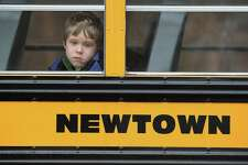 A child gazes from a school bus as it passes by the St. Rose of Lima Catholic church while mourners gathered for a funeral service for shooting victim Jessica Rekos, 6, on Dec. 18, 2012 in Newtown, Connecticut. Four days after 20 children and six adults were killed at Sandy Hook Elementary School, most students in Newtown returned to school. (Photo by John Moore/Getty Images)