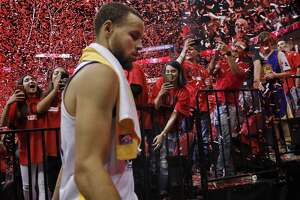Rockets fans cheer as Stephen Curry (30) walks off the court after the Golden State Warriors were defeated by the Houston Rockets 127-105 in Game 2 of the Western Conference Finals at Toyota Center in Houston, Texas, on Wednesday, May 16, 2018.