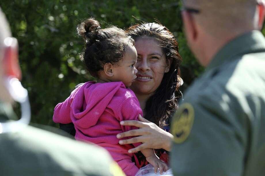 Honduran Patricia Rodriguez Hernandez, 22, holds her daughter, Denia Abigail, 1, after surrendering to U.S. Border Patrol agents near the Anzalduas International Bridge in Mission, Texas, Thursday, May 10, 2018. Photo: JERRY LARA / San Antonio Express-News / San Antonio Express-News