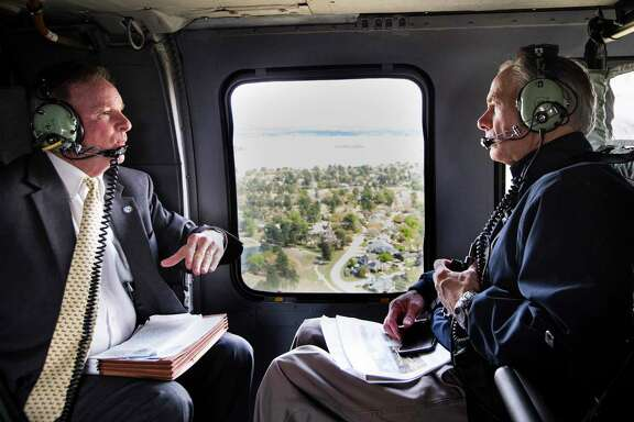 Gov. Greg Abbott, right, speaks with Dave Martin, the Houston city councilman representing heavily damaged Kingwood area during an aerial tour of neighborhoods devastated in the aftermath of Hurricane Harvey